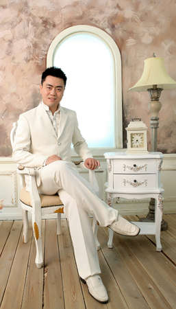Chinese young man in white suite sitting in chair in bright room photo