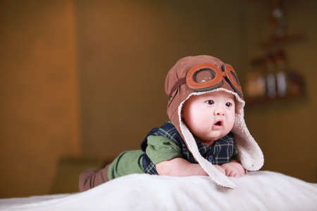 Renkli suit yatak oynayan Mutlu sevimli 3 aylık Çinli erkek bebek