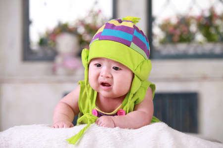 Happy cute 3-month old Chinese baby boy playing on bed with colorful suites