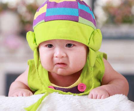Mutlu şirin 3 aylık Çinli bebek renkli suit yatakta oynarken