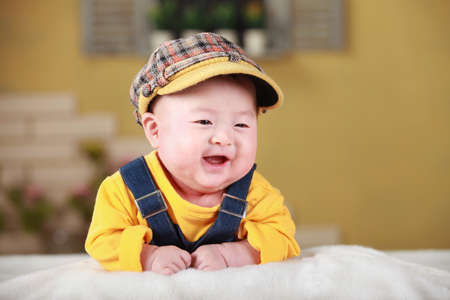 Happy cute 3-month old Chinese baby boy playing on bed with colorful suites photo