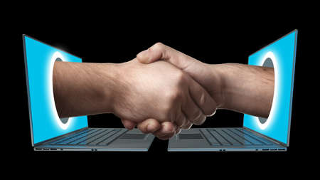 A hand comes right out of the laptop screen to shake hands CONCEPT. isolated on black background High resolution  photo
