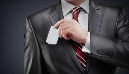 Hombre de negocios entrega una tarjeta en blanco sobre fondo gris de alta resoluci�n