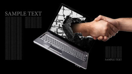 ecomerce: A hand scomes right out of the laptop screen to shake hands CONCEPT. isolated on black background High resolution  Stock Photo