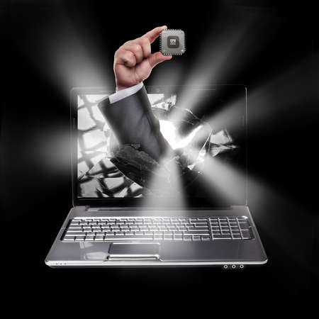 key punching: CONCEPT. laptop with broken screen and hand hand holds the processor CPU isolated on black background High resolution