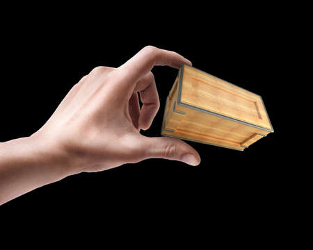 Mans hand holding wooden box isolated on black background photo