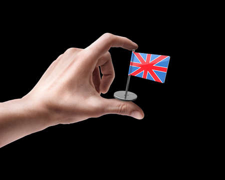 Mans hand holding UK flag isolated on black background  photo