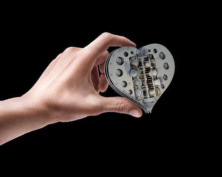 ferreteria: La mano del hombre la celebración de mecánica V8 de corazón aislado en el fondo negro Foto de archivo