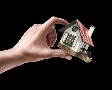 Mans hand holding house isolated on black background  photo