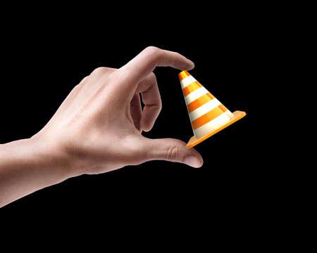 Mans hand holding Orange highway traffic cone isolated on black background  photo