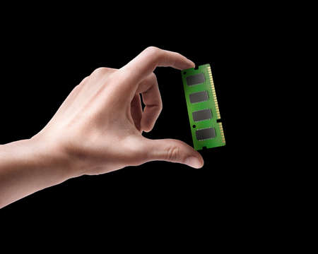 Mans hand holding Computer RAM Memory Card isolated on black background  photo