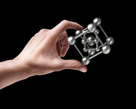 Mans hand holding molecules structure sphere isolated on black background photo