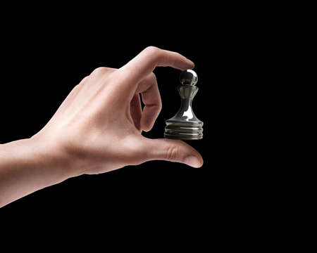 pawn adult: Mans hand holding chess Pawn isolated on black background