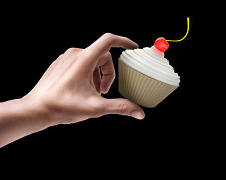 Mans hand holding cup-cake with creme fraiche and cherry isolated on black background  photo