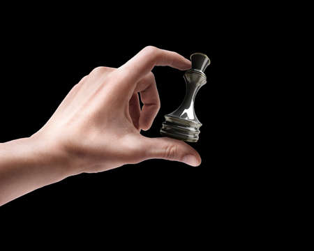 preferment: Mans hand holding chess Queen isolated on black background