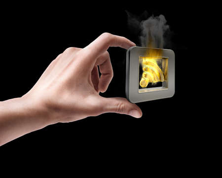 skin burns: Mans hand holding rss flaming icon isolated on black background  Stock Photo