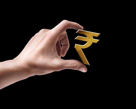 rupees: Mans hand holding Golden Indian rupee simbol isolated on black background  Stock Photo
