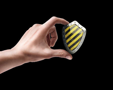 body dimensions: Mans hand holding Yellow and black shield isolated on black background