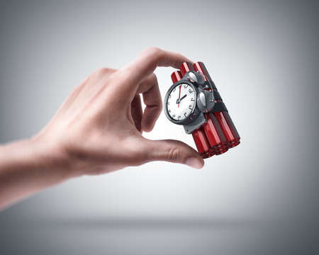 explosive sign: Mans hand holding Bomb with clock timer Stock Photo