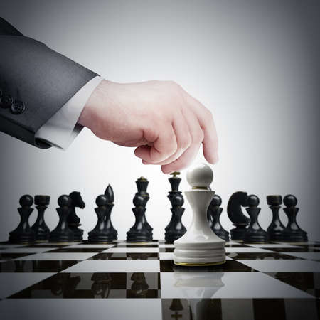 Strategy concept. hand holding white chess figure on chess board  photo