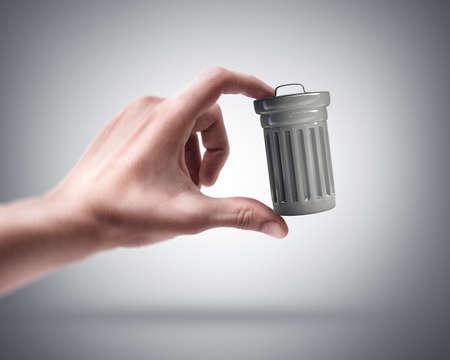 rubbish bin: Mans hand holding Steel trash can