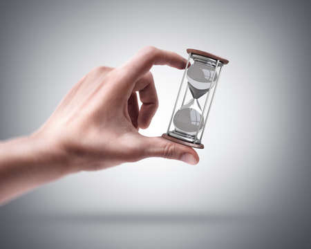 Mans hand holding hourglass