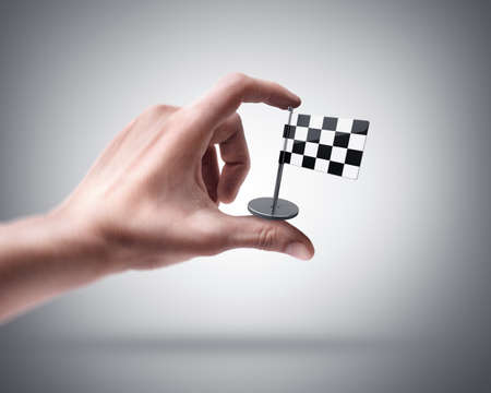 Mans hand holding Checkered Flag photo