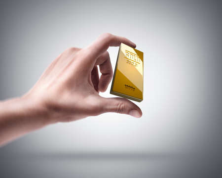 Man's hand holding golden bar photo