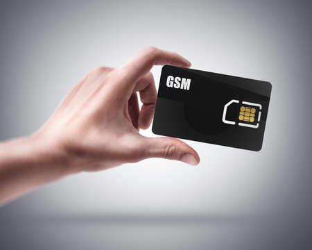 gsm: Mans hand holding black GSM sim card