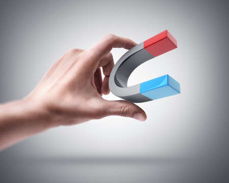 magnet: Mans hand holding magnet Stock Photo
