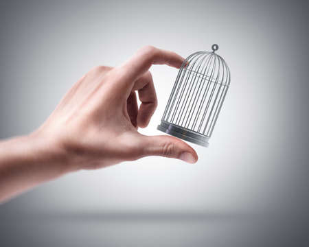spiralling: Mans hand holding empty cage Stock Photo