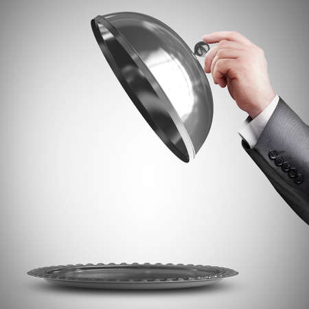 trays: businessman hand holding silver platter or cloche with space to place object  Stock Photo
