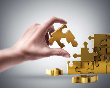 Mans hand holding golden puzzle Stock Photo