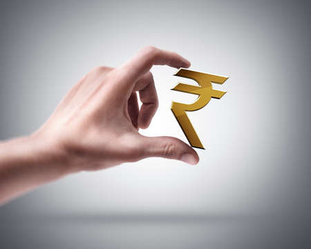 Man's hand holding Golden Indian rupee photo