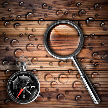 Antique brass compass and magnifying glass over wooden background High resolution  photo