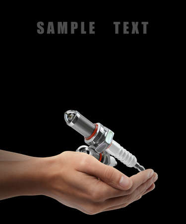 magneto: Spark plugs. Man hand holding object  isolated on black background. High resolution  Stock Photo