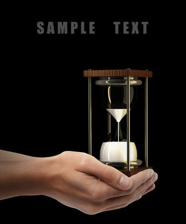 hourglass sand clock. Man hand holding object isolated on black background. High resolution  photo