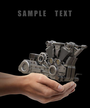 chromed motorcycle engine. Man hand holding object  isolated on black background. High resolution  Stock Photo