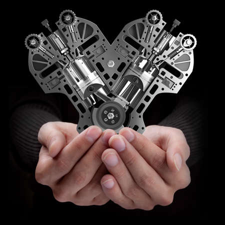 car body: Man hand holding object ( Car engine) isolated on black background. High resolution Stock Photo