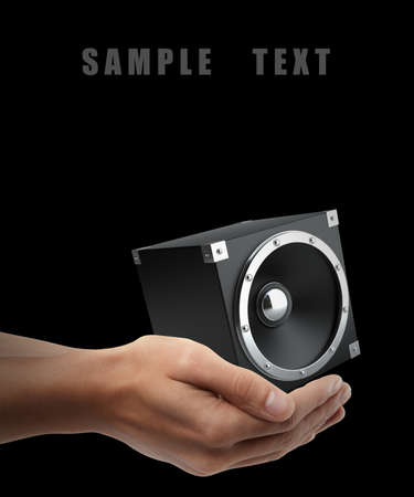 black speakers. Man hand holding object  isolated on black background. High resolution