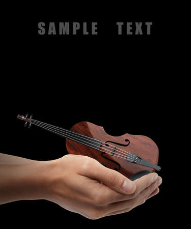 Classic violin. Man hand holding object  isolated on black background. High resolution