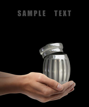 Steel trash can. Man hand holding object  isolated on black background. High resolution