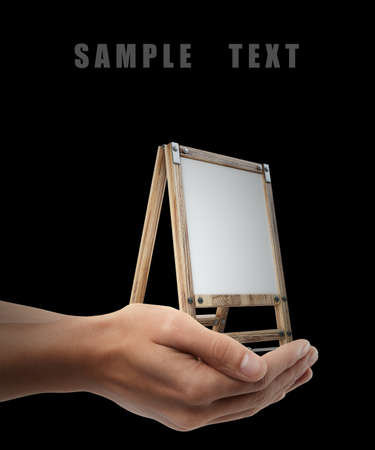 Blank Canvas on easel. Man hand holding object isolated on black background. High resolution  photo