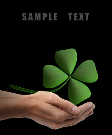 traditionally irish: Man hand holding object ( green clover ) isolated on black background. High resolution