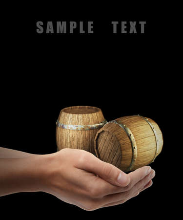 Wooden barrels. Man hand holding object isolated on black background. High resolution  photo