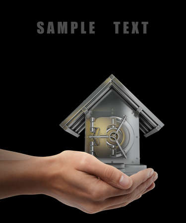 safe house: Man hand holding object ( Bank Safe in form houses ) isolated on black background. High resolution