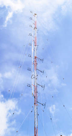 mobile phone transmitter antenna on blue sky background photo