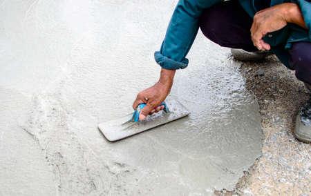 Man stukadoors een vloer met troffel. Bouwvakker Stockfoto