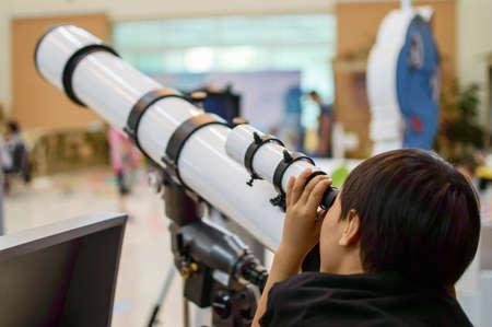 A boy watching through a telescope
