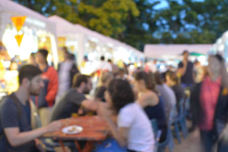 Blurred background of many people eating outside in the street
